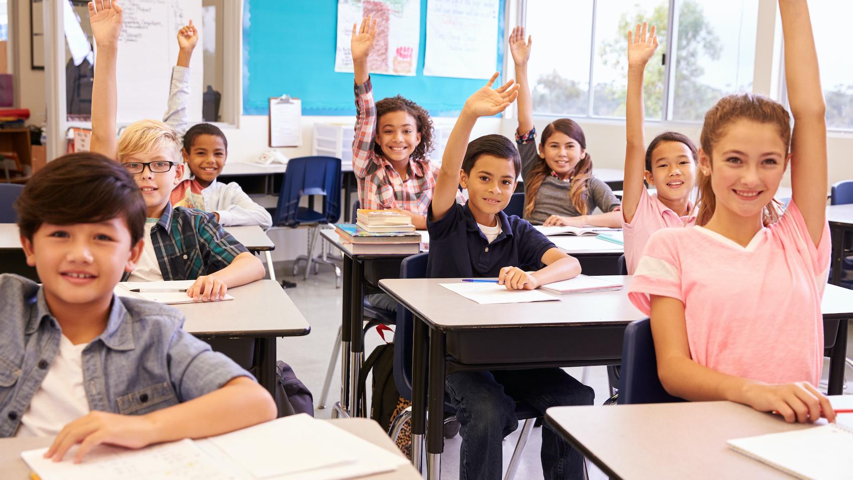 Elementary school kids in a classroom raising their hands.