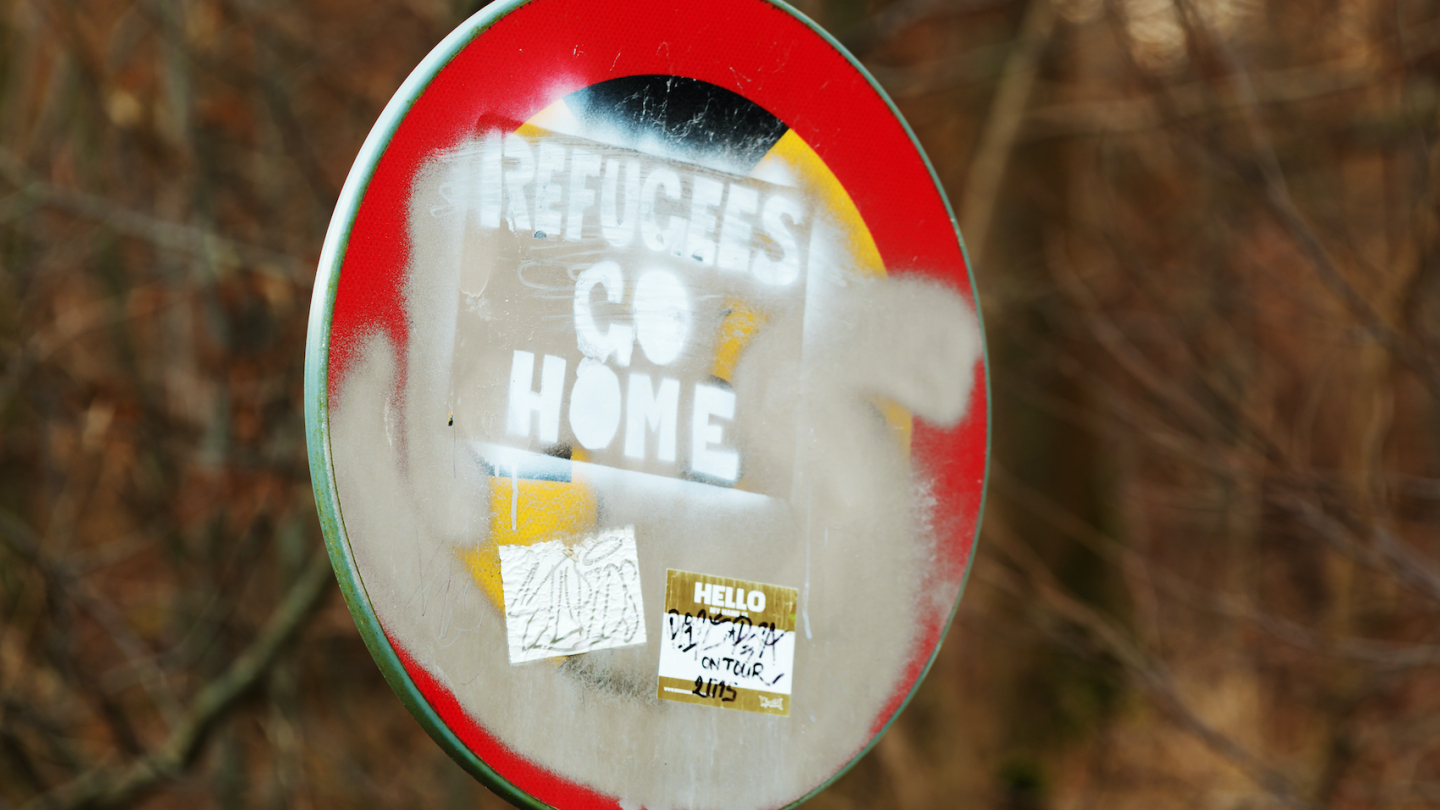 """Racist and hateful message saying """"Refugees Go Home"""", painted on a traffic sign with stickers and paint all over in Karlskrona, Sweden on January 13, 2016."""