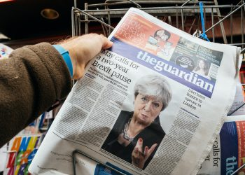 """Man buying The Guardian newspaper from press kiosk with Braking news from Theresa May British Prime Minister """"Brexit delayed two years"""" in Paris on September 25, 2017."""